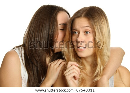 Two attractive young women friends isolated on white background. One girl whispers to another secret