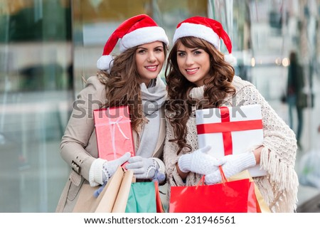 Two attractive young women shopping together,holding shopping bags and gift boxes,with red christmas hat,smiling while standing in front of shop window. Outdoors. - stock photo