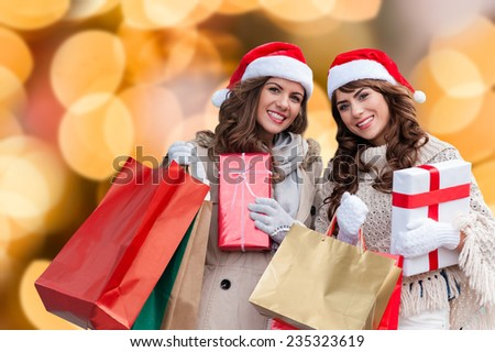 Two attractive young women shopping together,holding shopping bags and gift boxes,with red christmas hat,smiling over isolated christmas colorful lights background - stock photo