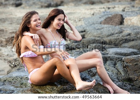 Two attractive young women sit on a rocky shore with their arms around each other. Horizontal shot.