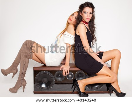 two attractive young women sitting on a loudspeaker back to back, white background - stock photo