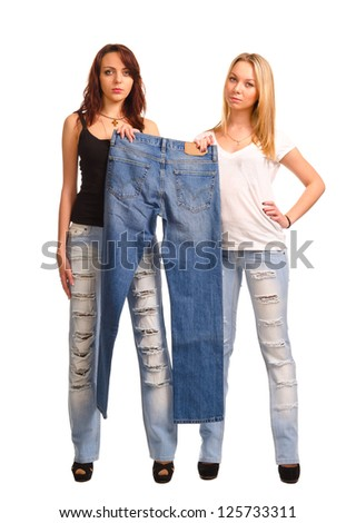 Two attractive young women standing side by side holding up a pair of blue denim jeans, studio portrait isolated on white - stock photo