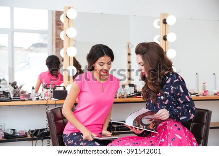 Two attractive young women using tablet and reading magazine in beauty salon - stock photo