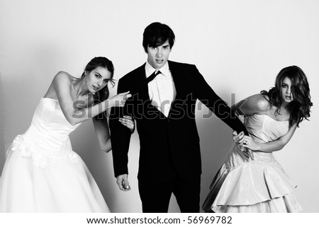 Two attractive young women wearing formal attire are pulling a young man in a suit between them. Horizontal shot.
