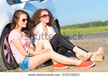 Two attractive young women wearing sunglasses, sitting next to the car