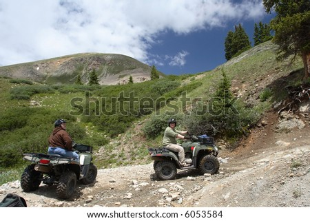Two ATV riders pause on a trail on Mt. Princeton in the Colorado Rockies - stock photo