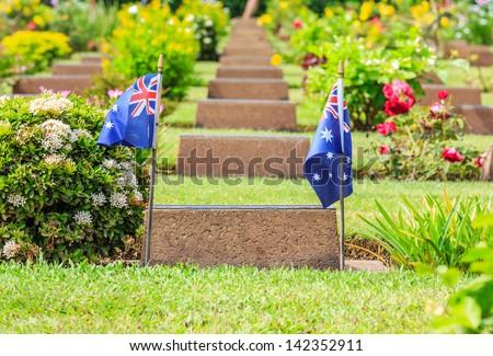 two australian flags on tomb, kanchanaburi war cemetery, thailand - stock photo