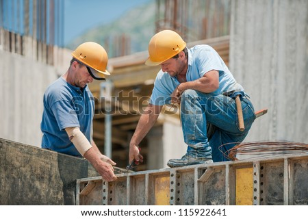 Two authentic construction workers collaborating in the installation of concrete formwork frames