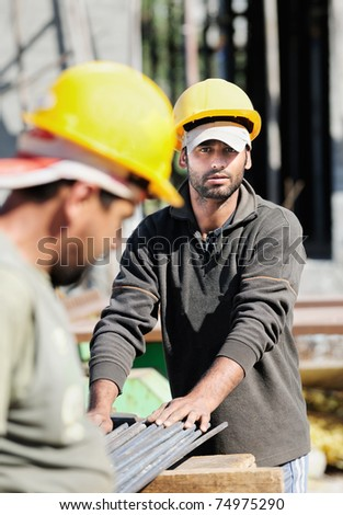 Two authentic construction workers, one of them looking at camera - stock photo
