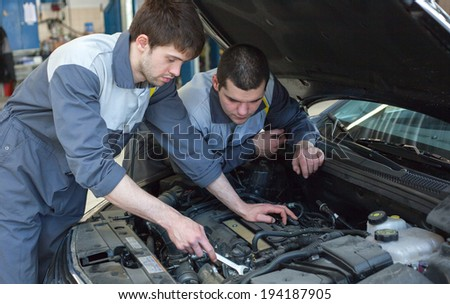 Two auto mechanics examining car with open hood.