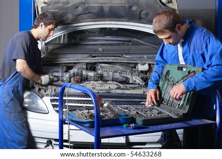 Two auto mechanics working at auto repair shop - stock photo
