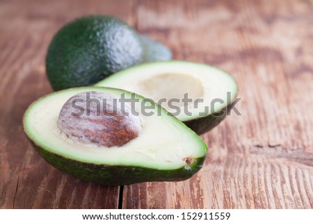 Two avocados on wooden background. Shallow dof - stock photo