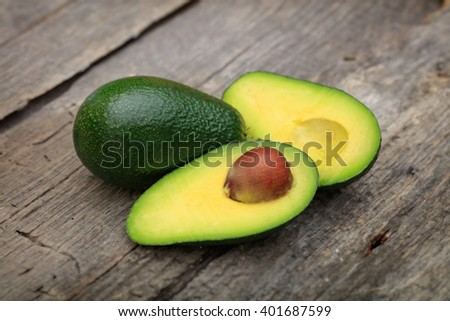 Two avocados one cut in two with seed, on wooden surface - stock photo