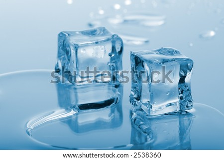 Two azure colored ice cubes melted in water on reflection surface ready to be added to a cocktail - stock photo