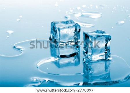 Two azure colored ice cubes melted in water on reflection surface ready to be added to a cocktail