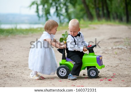 two babies - boy and girl dressed as bride and groom - play with toy car