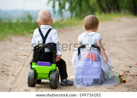 two babies - boy and girl dressed as bride and groom - sit on toy cars
