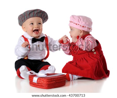 Two babies dressed up for Valentine's Day.  He's obviously delighted as he hold her hand.  Isolated on white. - stock photo