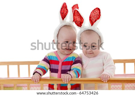 Two babies twins in bunny ears standing in the crib - stock photo