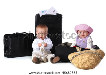 Two babies with their boarding pass, surrounded by suitcases.  The boy has his shoes in his hands.  Isolated on white. - stock photo