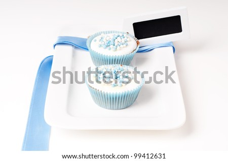 Two baby blue cupcakes on a plate with label and ribbon - stock photo