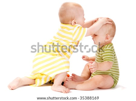 Two baby boys playing together, isolated, over white - stock photo