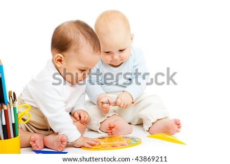 Two baby boys with paints, isolated