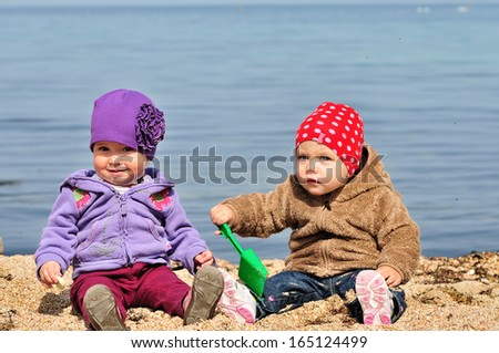 two baby friends playing on the sea shore - stock photo
