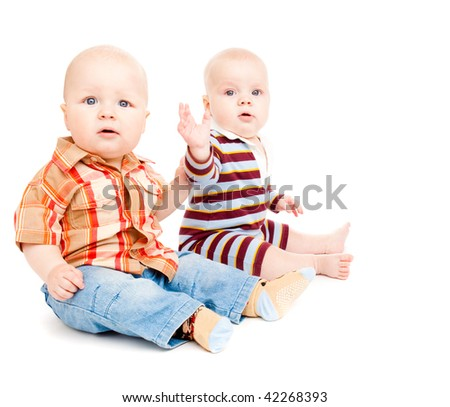 Two baby friends playing, over white - stock photo