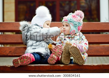two baby friends sitting on the bench - stock photo