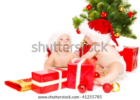Two baby friends with Christmas presents - stock photo