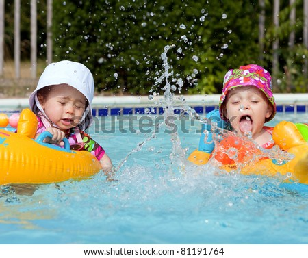 Two baby girls splashing water in a pool - stock photo