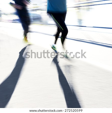 Two back lit joggers in blurred motion in bright sunshine casting long shadows - stock photo