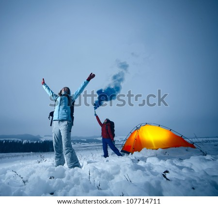 Two backpackers asking a help in a winter field - stock photo