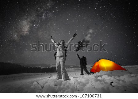 Two backpackers giving SOS signals in a winter field with night sky full of stars on the background