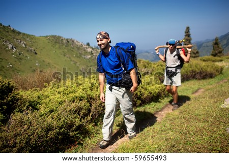 Two backpackers in the summer mountain - stock photo