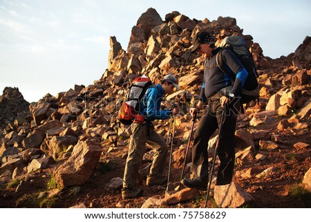 Two backpackers on footpath in morning mountains - stock photo