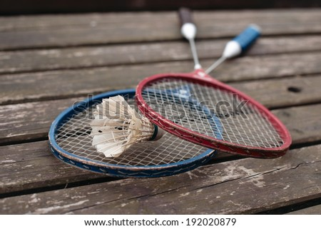 two badminton rackets on the old wooden table - stock photo