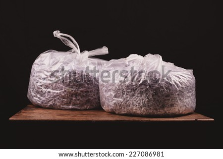 Two bags of shredded paper on a wooden table - stock photo