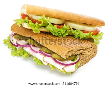 Two Baguette Sandwichies with lettuce, slices of fresh tomatoes, cucumber, ham, salami and cheese