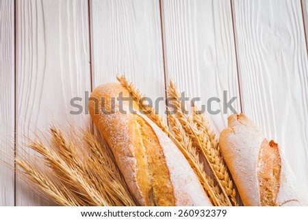 two baguettes and ears of wheat on white painted boards food and drink concept  - stock photo