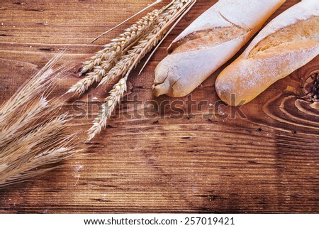 two baguettes and ears of wheat rye on vintage wooden board with copyspace food and drink concept  - stock photo