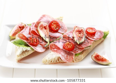 Two baguettes with lettuce, salami and fresh figs - stock photo
