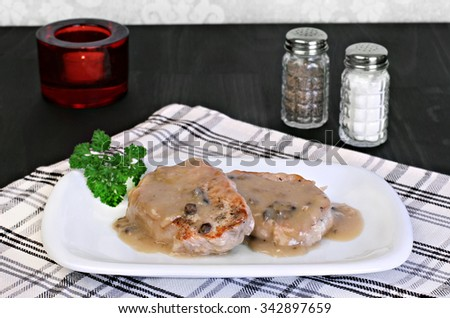 Two baked pork chops with mushroom gravy. - stock photo
