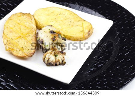 Two baked potatoes on plate with squid and white background - stock photo