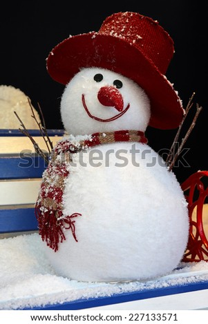 Two ball snowman sculpture with hat and scarf sitting at bench in park - stock photo