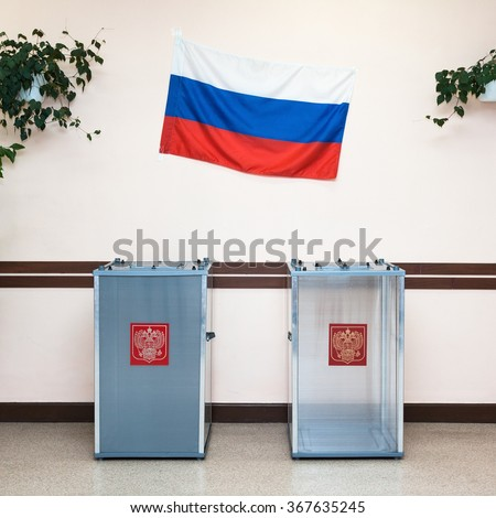 Two ballot boxes for voting in the elections with coat of arms Russian Federation and the national flag of Russia the hanging on the wall in the polling station. - stock photo