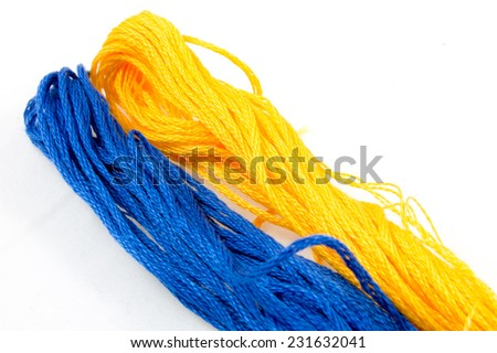 two balls of cotton blue and yellow - stock photo
