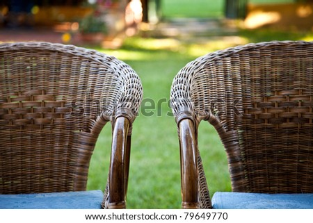 Two bamboo chairs in garden - stock photo