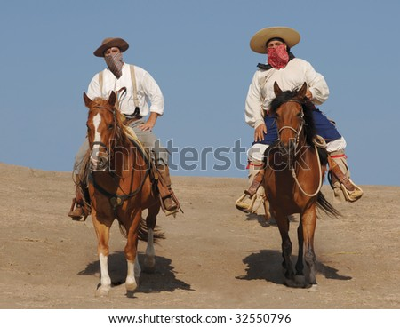 Two banditos riding on horses